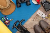 vrchní pohled na turistické vybavení na modrém podložce na spaní, foto kamera, boty a klobouk na dřevěném povrchu