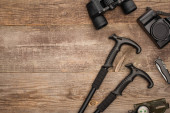 top view of trekking poles, binoculars, photo camera, compass and jackknife on wooden surface