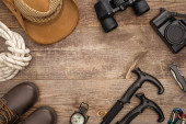 top view of hiking equipment, boots, hat and photo camera on wooden surface
