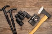 Ansicht von Wanderstöcken, Ferngläsern, Fotokamera und Axt auf Holzoberfläche