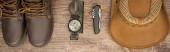 panoramatický snímek bot, kompasu, nože a klobouku na dřevěném stole