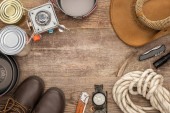 top view of gas burner, metal dishes, tin cans, boots, hat and hiking equipment on wooden surface