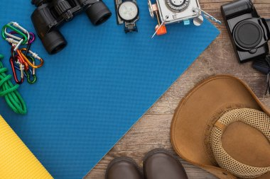 Top view of hiking equipment on blue sleeping mat, photo camera, boots and hat on wooden surface stock vector