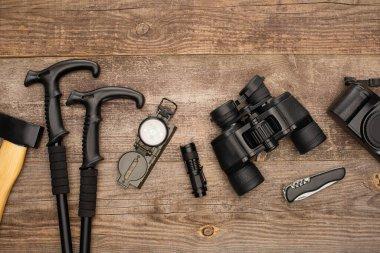 Top view of axe, trekking poles, compass, flashlight, binoculars, jackknife and photo camera on wooden table stock vector