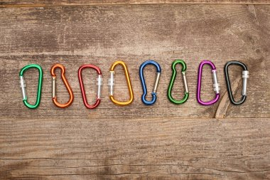 Top view of colorful carabiners in row on wooden table stock vector