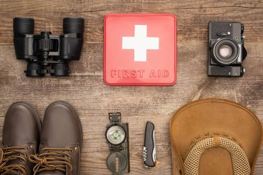 Top view of red first aid kit, binoculars, photo camera, boots, hat, compass and jackknife on wooden surface stock vector