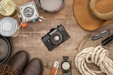 Top view of photo camera, hat, boots and hiking equipment on wooden table stock vector