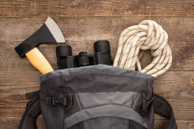 top view of backpack with axe, hiking rope and binoculars on wooden surface