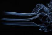 Photo white flowing smoke cloud on black background