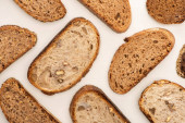 top view of tasty whole wheat bread slices on white background