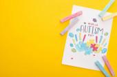 Fotografie Karte mit Puzzle und Handabdrücken zum Welt-Autismus-Tag isoliert auf gelb mit bunten Kreiden