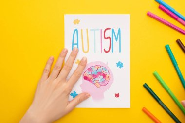 top view of person holding paper sheet with autism lettering and drawing of child near felt pens on yellow