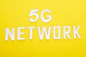 Fotografie Draufsicht auf weißen 5g Netzwerk-Schriftzug auf gelbem Hintergrund