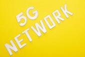 Draufsicht auf weißen 5g Netzwerk-Schriftzug auf gelbem Hintergrund