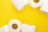 Fotografie Draufsicht auf weiße Toilettenpapierrollen auf gelbem Hintergrund mit Kopierraum