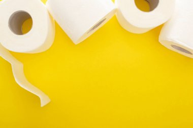 Top view of white toilet paper rolls on yellow background with copy space stock vector