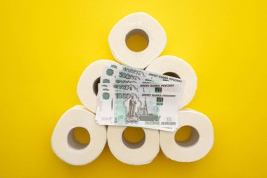 Top view of white toilet paper rolls arranged in pyramid with russian money on yellow background stock vector