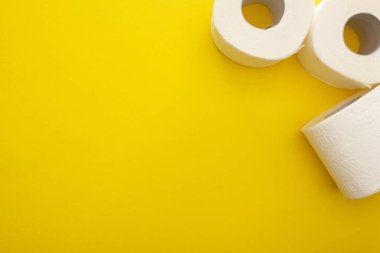 Top view of clean toilet paper rolls on yellow background with copy space stock vector
