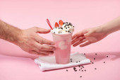 Photo Partial view of female and male hands with disposable cup of strawberry milkshake with chocolate morsels on napkins on pink