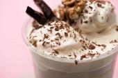 Selektivní zaměření jednorázového šálku mléčného koktejlu se zmrzlinou, vlašskými ořechy, kousky čokolády a kousky na růžové