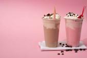 Jednorázové šálky čokolády a jahodových mléčných koktejlů s pitnou slámou a kávovými zrny na ubrouscích na růžové