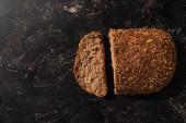 vrchní pohled na krájený celozrnný chléb na kamenném černém povrchu