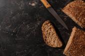 vrchní pohled na krájený celozrnný chléb a nůž na kamenném černém povrchu