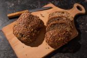 vágott teljes kiőrlésű kenyér vágódeszkán kés közelében, kő fekete felületen