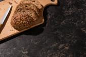 Fotografie Ansicht von geschnittenem Vollkornbrot auf Schneidebrett in Messernähe auf steinschwarzer Oberfläche
