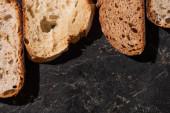 vrchní pohled na čerstvé pečené plátky chleba na kamenném černém povrchu
