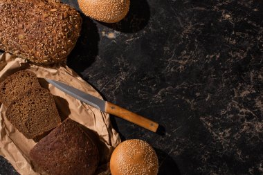 top view of fresh cut and whole bread with knife on stone black surface