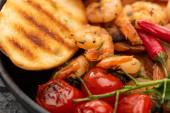 zblízka pohled na smažené krevety s grilovaným chlebem, rajčaty, chilli papričkami