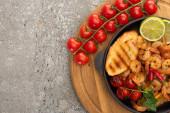 vrchní pohled na smažené krevety s grilovanými tousty, zeleninou, cherry rajčaty a limetkou na dřevěné desce na šedém betonovém pozadí