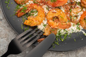 close up view of fried shrimps in sauce with dill in black plate on grey concrete background with cutlery