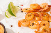 Photo close up view of fried shrimps with lime and pepper on white parchment paper