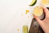 vágott kilátás nő iszik arany tequila lime, só fehér márvány felületen