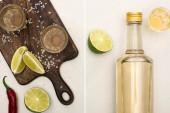 arany tequila kollázs üvegben és feles poharakban lime-mal, chili paprikával, fehér márvány felületen fa vágódeszkán lévő só