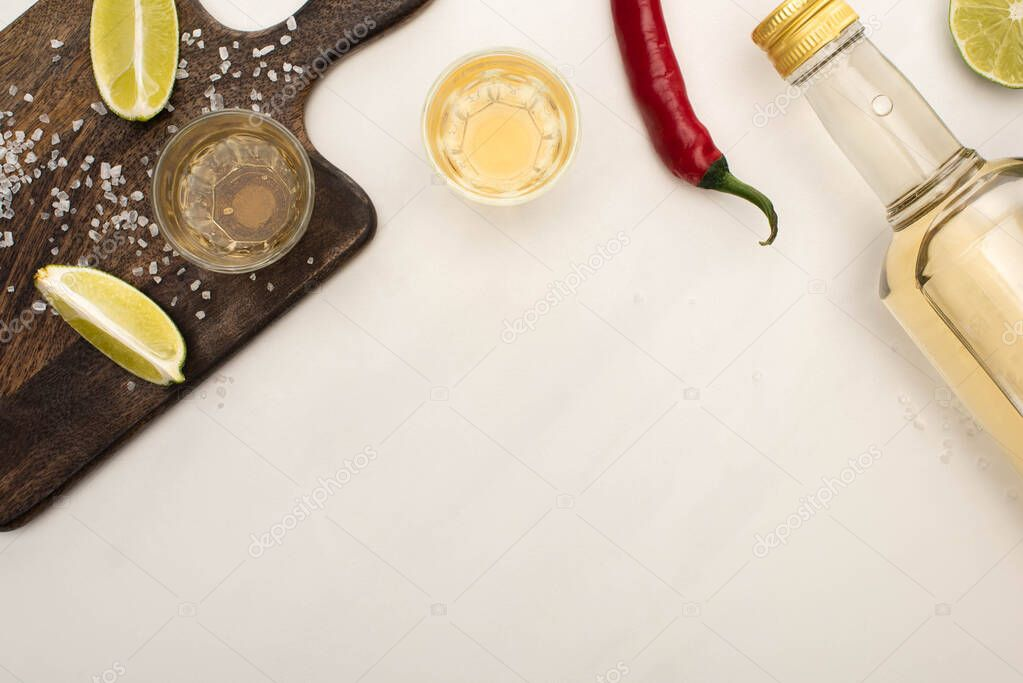 Top view of golden tequila with lime, chili pepper, salt on wooden cutting board on white marble surface stock vector