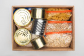 top view of cans and groats in zipper bags in wooden box on white background, food donation concept