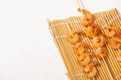 top view of prawns on skewers on bamboo mat on white background
