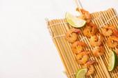 Fotografie horní pohled na krevety na špejle s vápnem na bambusové podložce na bílém pozadí
