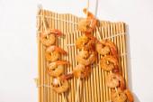 horní pohled na krevety na špejle na bambusové podložce na bílém pozadí