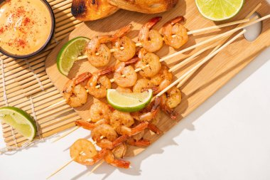 Top view of prawns on skewers with lime and sauce on bamboo mat on white background stock vector
