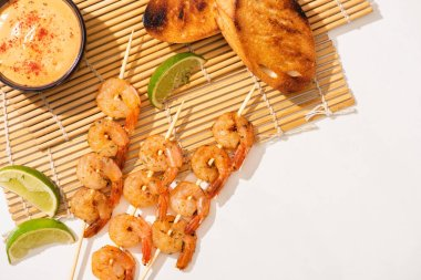 Top view of prawns on skewers with toasts, lime and sauce on bamboo mat on white background stock vector