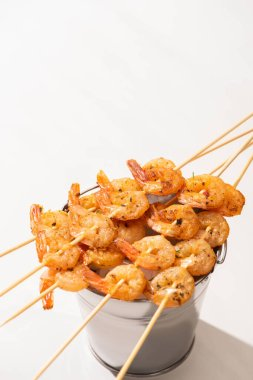 Prawns on skewers on metal bucket on white background stock vector