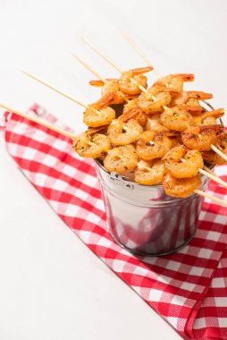 prawns on skewers on metal bucket and plaid napkin on white background
