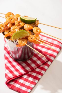 prawns on skewers with lime on metal bucket and plaid napkin on white background