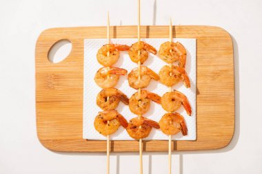 Top view of fried prawns on skewers on wooden board on white background stock vector