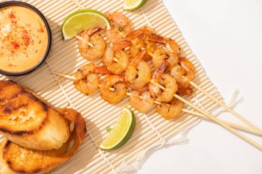 Top view of prawns on skewers with grilled bread, lime and sauce on bamboo mat on white background stock vector