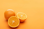 ripe delicious cut and whole oranges on colorful background